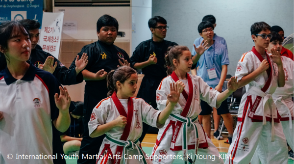Youth in martial arts postures at the IYMAC